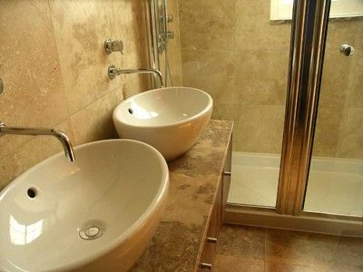 White his and her matching sinks in a brown stone bathroom serviced by Able Plumbing Repair Service, Inc. in Orange Park, FL
