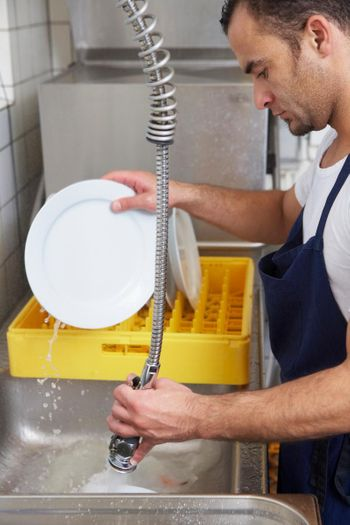 Male cleaning dishes in a professional kitchen sink serviced by Able Plumbing Repair Service, Inc. in Orange Park, FL